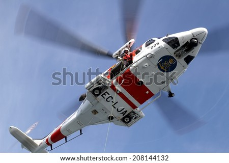 ALICANTE COAST, SPAIN - JULY 5: The helicopter of the Spanish  Maritime Rescue Team and his rescuers training over the deck of a coast guard ship, on july 5, 2014 in Alicante coast. - stock photo
