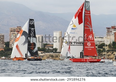 """ALICANTE, SPAIN - OCTOBER 04: The sail boat of the Team Alvimedica and Dongfeng are sailing in the """"Volvo Ocean Race 2014-2015"""" in-port race in Alicante bay, on october 04, 2014 in Alicante. - stock photo"""