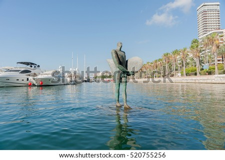ALICANTE, SPAIN - SEPTEMBER 9; Icarus with broad shoulders with little head carrying a surf board in marina harbor, September 9, 2016,  Alicante, Spain