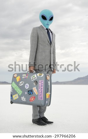 Alien businessman traveling with suitcase plastered with souvenir stickers on aerospace voyage to dramatic other worldly lunar landscape  - stock photo