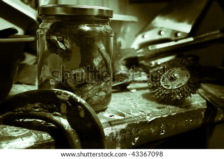 alien embryo in a jar on work bench with tools - stock photo
