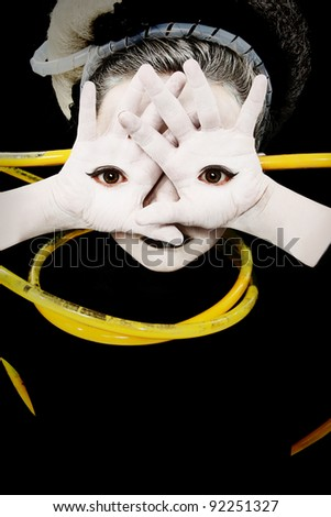 Alien girl child portrait with eyes on palms of hands and yellow tubes attached. - stock photo