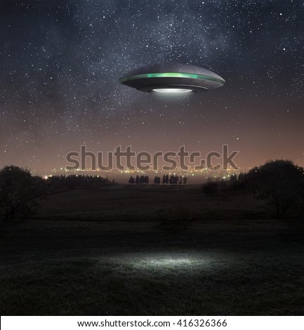 Alien spacecraft is hovering above the meadow - stock photo