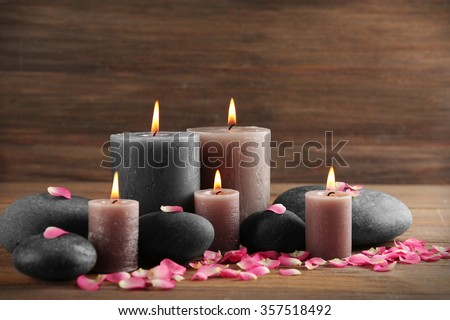 Alight wax grey candle with flower petals and pebbles on wooden background - stock photo