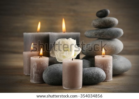 Alight wax grey candle with pebbles and beautiful flower on wooden background - stock photo