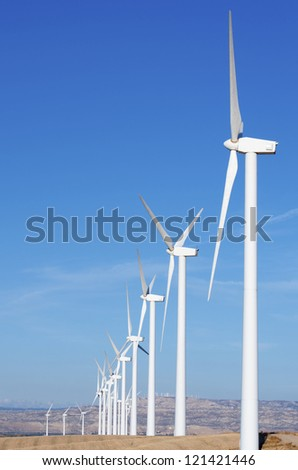 aligned group of windmills for electric power production in Pozuelo de Aragon, Saragossa, Aragon, Spain