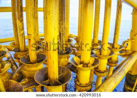 Aligned Oil and Gas Production slots (Dirty pipe) on the sea background in Offshore wellhead remote platform, Energy and petroleum industry. - stock photo