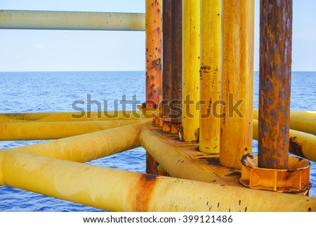 Aligned Oil and Gas Production slots (Rust pipe) on the sea background in Offshore wellhead remote platform, Energy and petroleum industry. - stock photo