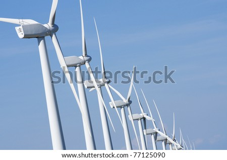 aligned windmills for renovable electric production - stock photo