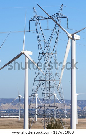 aligned windmills for renowable electric production and power line, Pozuelo de Aragon, Zaragoza, Aragon, Spain