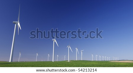 aligned windmills in an idyllic green meadows and clear sky - stock photo
