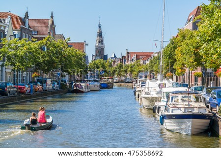 ALKMAAR, NETHERLANDS - AUG 17, 2016: Boats on Luttik Oudorp canal and weigh house tower in Alkmaar, North Holland, Netherlands