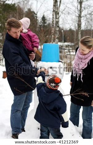 All family making snowman in winter park - stock photo
