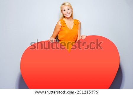 All my heart is for you. Beautiful young blond hair woman in pretty dress looking at camera holding hands on huge red heart and smiling while standing against grey background   - stock photo