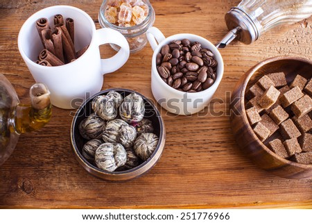 All object for green tea ceremony cinnamon sticks  Cane granulated Sugar bowl candy cubes lie on round wooden plate coffee beans Old retro vintage aged wooden board table Transparent glass kettle  - stock photo