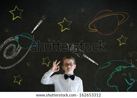 All ok or okay sign boy dressed up as business man with chalk universe planet solar system on blackboard imagining space travel - stock photo