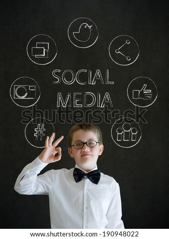 All ok or okay sign boy dressed up as business man with social media icons on blackboard background - stock photo