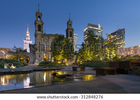 All Saints' Church at Grzybowski Square with skyscrapers in the downtown of Warsaw, Poland