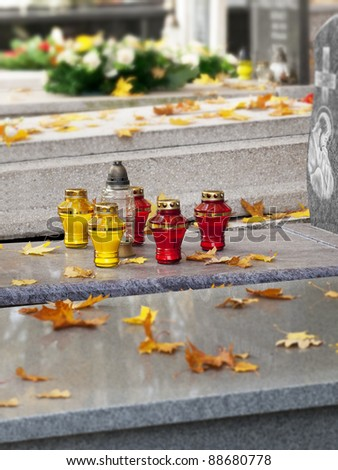 All Saints' Day in Poland. Autumn leaves and candles on Christian graves. - stock photo
