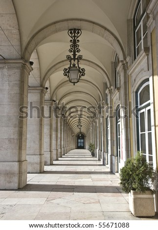 All the buildings surrounding three sides of the Commerce Square have arcades on the groundfloor, decorated with beautiful ceiling lamps and marble floors - stock photo