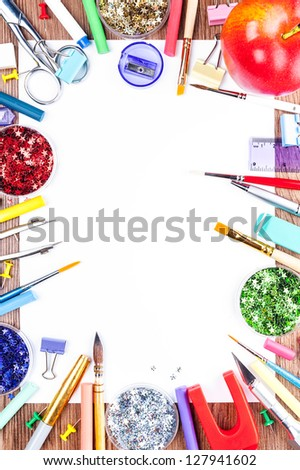 All the decorating and painting. White sheet of paper, surrounded by tools for drawing and big red apple. - stock photo