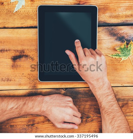 All the world in one touch. Close-up of man holding his finger on digital tablet while sitting at the wooden table outdoors - stock photo