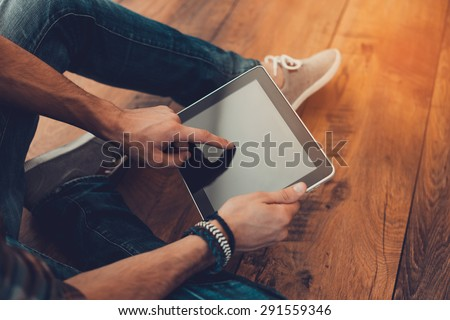 All the world in one touch. Close-up top view of man using digital tablet while sitting on the wooden floor - stock photo