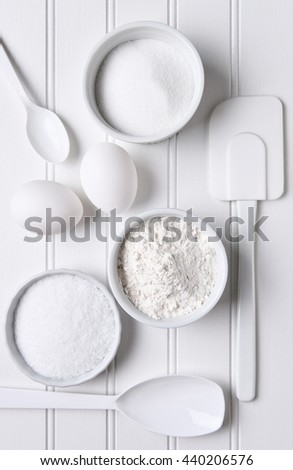 All white baking still life. Items include: spatula, whisk, eggs, flour, salt, sugar, bowls and spoons.Vertical format shot from a high angle. - stock photo