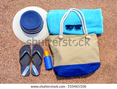 All you need for a summer vacation at the beach with a sunhat, flip flops, towel, sunglasses, sunscreen and beach bag neatly laid out on a sandy tropical beach, overhead view - stock photo