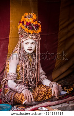 ALLAHABAD, INDIA - FEB 13 - An elaborately dressed holy man sits in his tent during the festival of Kumbha Mela on February 13th 2013 at Allahabad, India. - stock photo