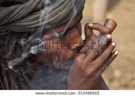 ALLAHABAD, INDIA - FEBRUARY 07, 2013:  A unidentified sadhu is smoking ganja (marihuana) with chillum at the Kumbha Mela religious festival - stock photo