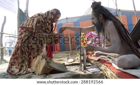 Allahabad, India, Jan 30, 2013.a naked ash covered naga baba sprinkles some holy ash into the palms of a young devotee woman in a sari during the Kumbh Mela. - stock photo