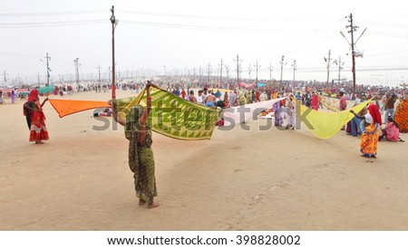 ALLAHABAD, UTTAR PRADESH, INDIA - FEBRUARY 07, 2013: Women put their sari out to dry on wind after ritual holy bathing in the Ganges river during the festival Kumbh Mela  - stock photo