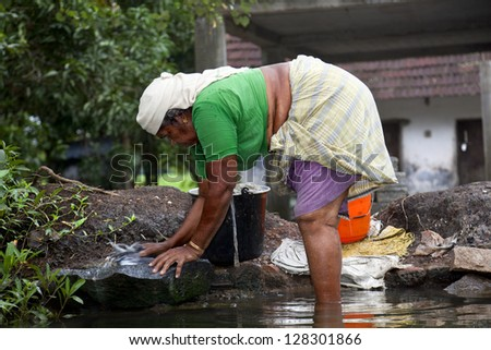 ALLEPY-SEPTEMBER 2012: An Indian woman washes her clothes on a rock in one of the canals around Alappuzha on september 7, 2012 in Allepy, India.