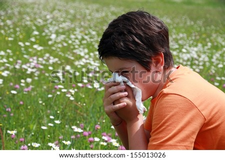 allergic child to pollen and flowers with a handkerchief while sneeze in the middle of the Minesweeper - stock photo