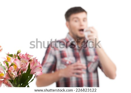 allergy man blowing his nose in tissue paper. Man blowing his nose isolated on white background  - stock photo