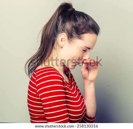Allergy sneeze Young woman scratch nose in fashion stripes clothes hipster casual posing on light background   - stock photo