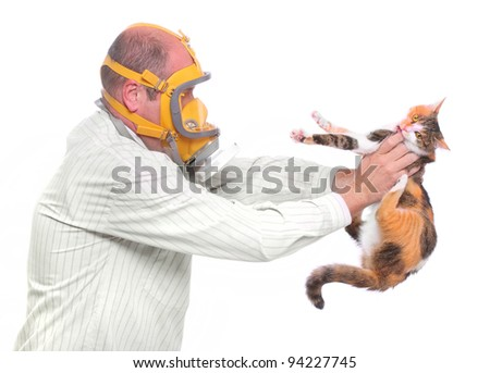 Allergy to animal fur concept. Male scientist in respirator holding test cat. - stock photo