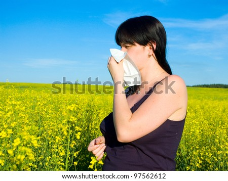 Allergy / Young woman blowing her nose on the rapeseed field - stock photo