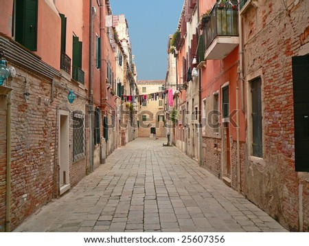 alley in venice leading to a residential area beneath a blue sky