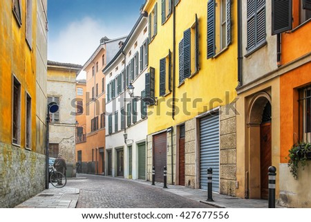 Alley with old colorful architecture in Parma, Emilia-Romagna province, Italy. Parma is famous for its prosciutto (ham), cheese, architecture and music. - stock photo