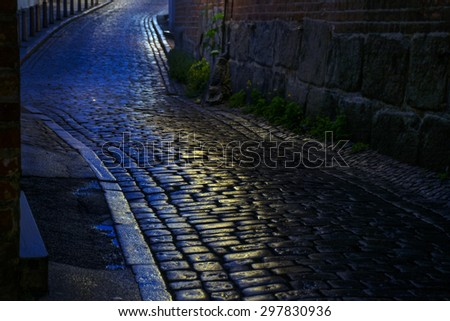 alley with wet cobblestones at night in an old town, narrow depth of field - stock photo