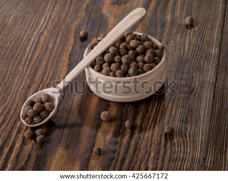 allspice in a spoon on a table - stock photo