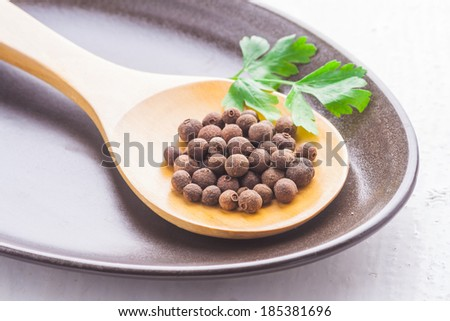 allspice on wooden spoon