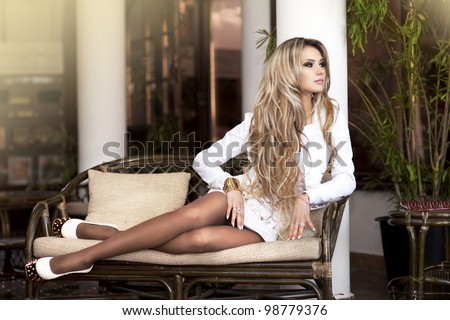 alluring blond relaxing on sofa in luxury interior. Stylish rich slim girl in sexy dress with healthy glossy hair at hotel villa apartment. Fashion glamorous shot at vacation resort spring-summer - stock photo