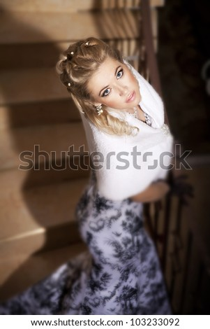 alluring blond woman relaxing on ladder in luxury hotel. Stylish rich slim girl in gloves  elegant dress and fur with healthy glossy hair at villa apartment. Fashion glamorous  model spring-summer - stock photo