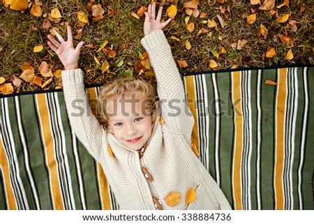 Alluring curly blond girl in beige knitted sweater smiling while lying on a striped rug on the background of autumn leaves - stock photo