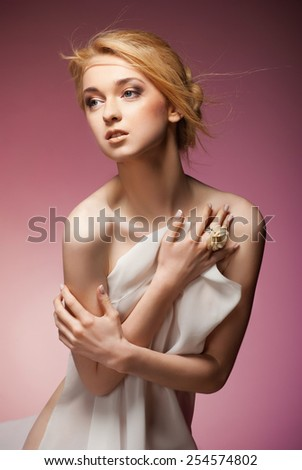 Alluring naked woman covering her breast with white cloth. Isolated over pink background - stock photo