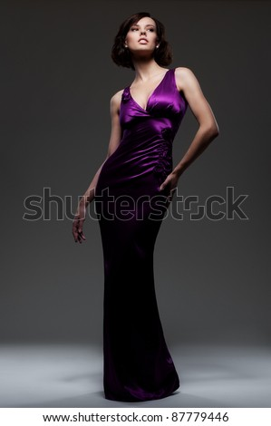 alluring sexy woman in evening dress posing over dark background