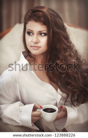 Alluring sexy woman in man boyfriend shirt at home with coffee at morning. Brunet girl with gorgeous long hair bright makeup and hairstyle in erotic wear holding a cup of hot aroma espresso. tonality - stock photo